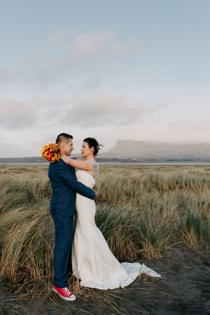 Newly married couple posing with Benbulben mountain in Sligo, Ireland